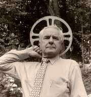 Adolfas Mekas holding a film reel behind his head like an angel halo
