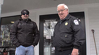 Chief Mooney stands in front of a store with an undercover detective