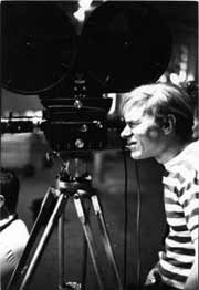 A young Andy Warhol looking through the viewfinder of his 16mm bolex camera