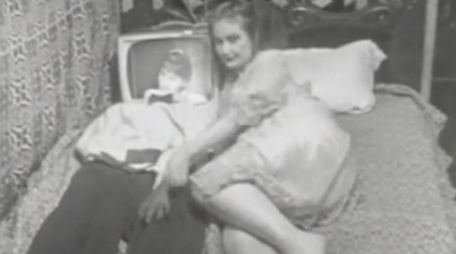 Woman lying in bed next to a man with a TV for a head