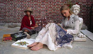 Two teenage sisters in hippie attire sketch artwork while sitting outside