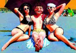 Man and two women in bikinis relax on the beach