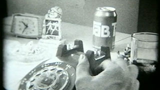 Man dialing a rotary phone while drinking a Tab