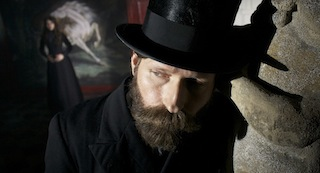 Crispin Glover with a thick beard and stovepipe hat