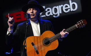 Musician Nenad Bach performing with an acoustic guitar
