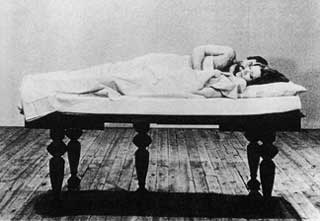 Man and woman lie in a raised bed off the floor