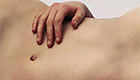 Woman's naked abdomen with a hand lying over it