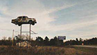 Car sitting on top of a tall tower in an abandoned field