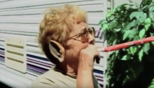Elderly woman wearing an elf ear blowing on a party favor in a trailer park