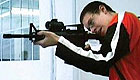 Teenage boy shooting a rifle