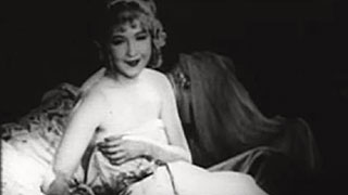 Still from old silent movie of a woman sitting in bed