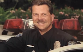 Ben Mihm smiles in his police uniform and cruiser