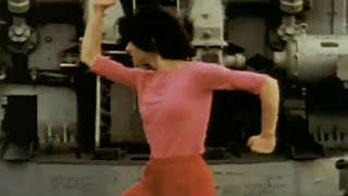 Woman in pink outfit dancing in front of heavy machinery