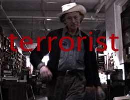 "Filmmaker Jonas Mekas strutting with the word ""terrorist"" superimposed over him"