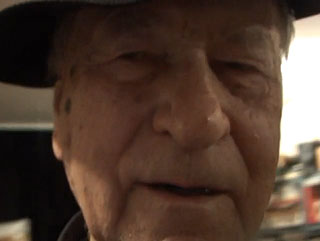 Close up image of Jonas Mekas making a video self-portrait
