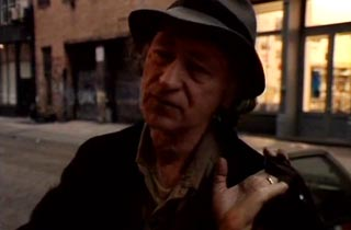Jonas Mekas giving an interview while standing on Wooster St. in New York City