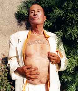 Kenneth Anger bares his chest showing his Lucifer tattoo