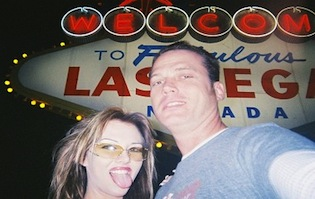 Adult film star Joe Blow and his girlfriend pose in front of the Las Vegas sign
