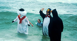 People dressed as penguins and a snowman stand in the freezing ocean