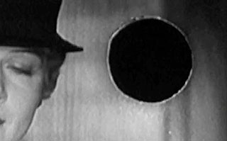 Old movie frame with a woman wearing a hat and a projectionist burn