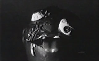 Black and white image of a ball with a grotesque face
