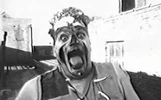 Black and white image of a man with a painted face sticking his tongue out
