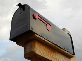 A mailbox with a red handle
