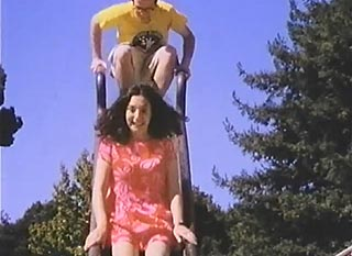 Two twentysomethings sliding down a playground slide on a date