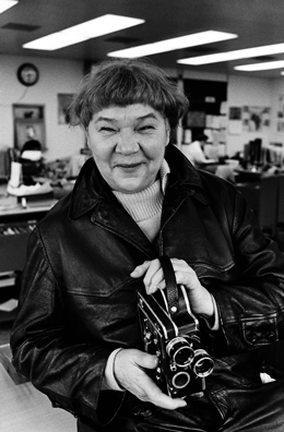 Portrait of filmmaker and painter Marie Menken holding a Bolex movie camera