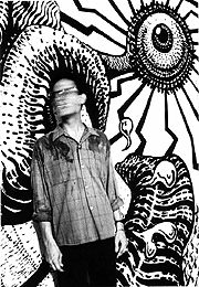 Black and white photo of Charles Pinion standing in front of a mural he painted