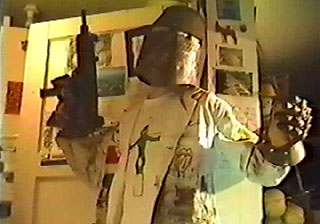 Guy wearing a metal helmet and iron glove while holding an uzi