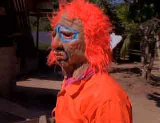 Man wearing a Halloween fright mask with an orange wig