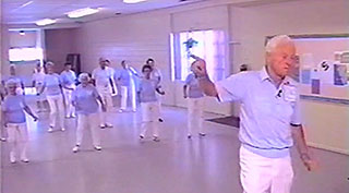 Elderly man leading elderly women in an exercise dance class