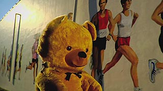 Teddy bear walks alongside a mural of joggers