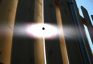 Black sun peeks through fence slats