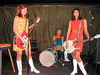 Three girl rock combo band perform on stage