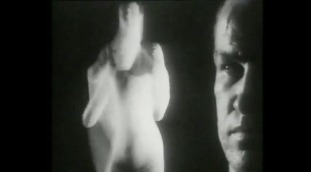 Film still of Thanatopsis featuring a close-up of a man's face looking at a blurry dancer