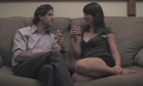 Pretty girl and nicely dressed man flirt with each other on a couch
