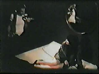 Film still from Black Box by Beth B and Scott B featuring a woman being interrogated in a dark room