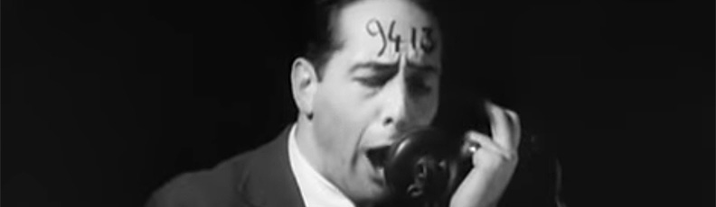 A man with the number 9413 written on his forehead yells into a telephone in Robert Florey/s film The Life and Death of 9413 — A Hollywood Extra.