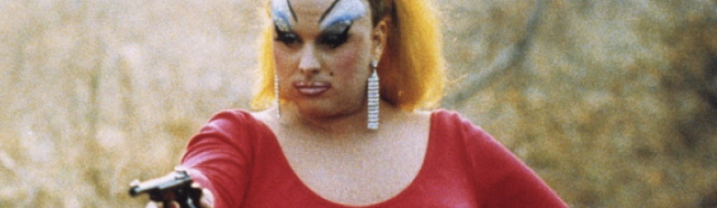 Divine points a gun in a still from the John Waters movie Pink Flamingos