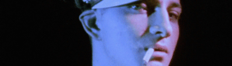 A biker smoking a cigarette gazes into the camera in a still from the Kenneth Anger film Scorpio Rising