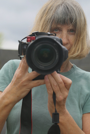 Portrait of filmmaker Vivienne Dick holding a camera