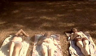 Three teenage girls lie on blankets outside on a patch of grass