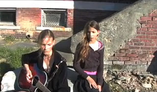 Two musical sisters sing and play guitar